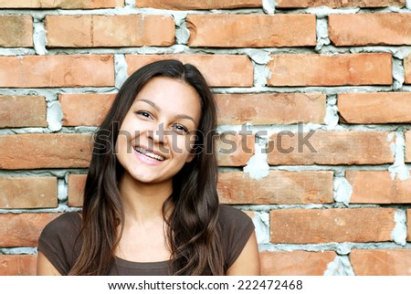 caucasian young beautiful teenage girl portrait over brick wall