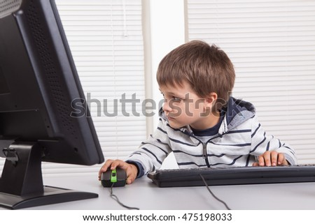 Caucasian young boy in office working on computer