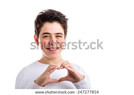 Caucasian young boy with acne-prone skin. in a white long sleeved t-shirt smiles making hand heart gesture