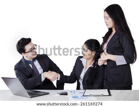 Caucasian young businessman shaking hands with his colleague on the table, isolated on white - stock photo