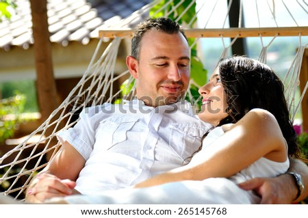 Caucasian young couple dressed in white on a rope hammock on the terrace of a country house lovingly looking fontal view - stock photo