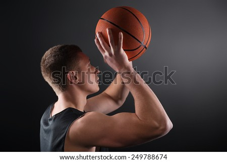 Caucasian young male basketball player free throwing the ball on black background - stock photo