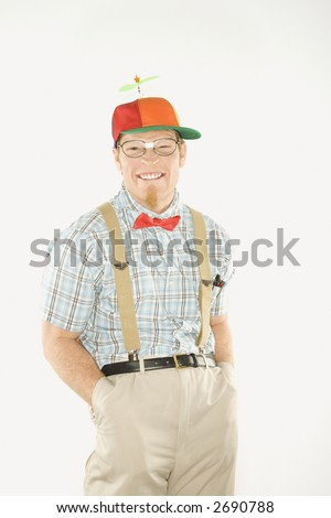 Caucasian young man dressed like nerd wearing propeller cap with hands in pockets looking at viewer with big smile.