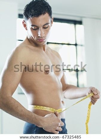 caucasian young man measuring waist with yellow tape. Vertical shape, waist up, side view, copy space - stock photo