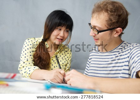 Caucasian young man talking with a Chinese girl is language teacher