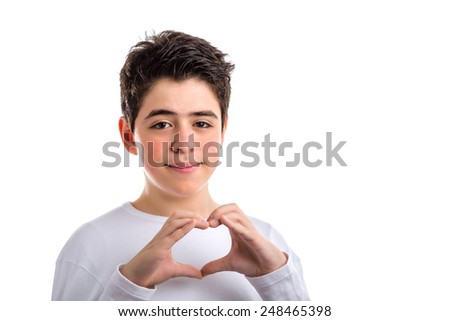 Caucasian young Smooth-skinned boy in a white long sleeved t-shirt smiles making hand heart gesture