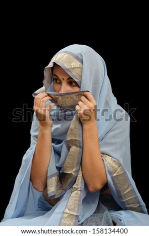 Caucasian young woman is wearing a traditional dress of women in the Indian Subcontinent. She is hiding her face and looking by stealth.