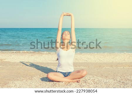 Caucasian young woman practicing yoga or fitness at seashore at sunset - stock photo