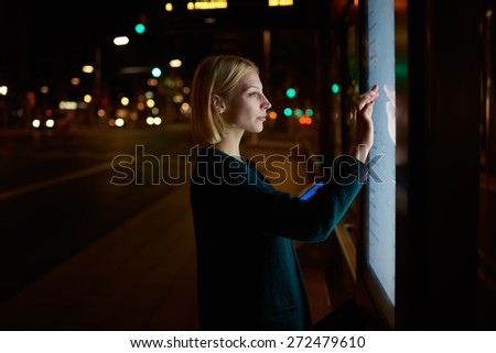 Caucasian young woman verifies account balance on banking application via modern kiosk with digital sensitive screen, charming female touching big digital display with reflected on her screen light - stock photo