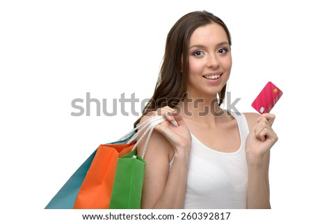 Caucasian young woman with colorful paper bags. She holding credit card and looking at camera. Concept for shop sales. Isolated on white background
