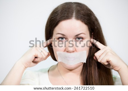 Caucasian young woman with glued tape on her mouth and closed ears, grey background - stock photo