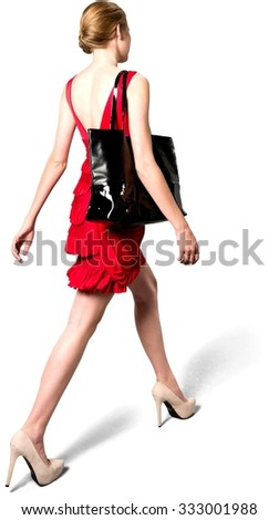 Caucasian young woman with medium blond hair in evening outfit walking - Isolated