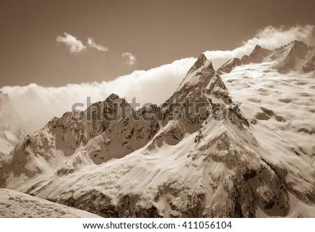 Caucasus Mountains, region Dombay. Peak Ine. View from ski slope. Sepia toned.  - stock photo