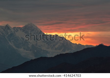 Caucasus mountains silhouettes at the rising sun. Warm yellow and orange abstract background. Svaneti, Georgia.