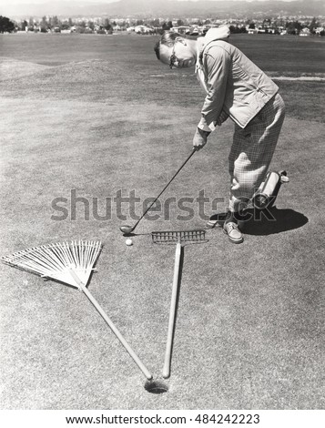 Caught between a rake and a gardening fork on the putting green