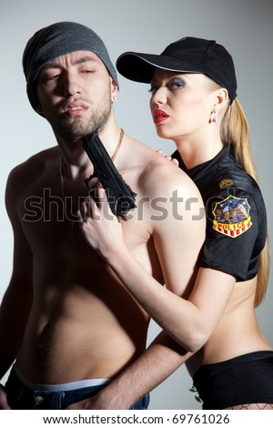 Caught criminal and police girl, close up studio shot