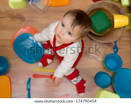 Caught in the Act - Adorable baby girl pulling pots and pans and other dishes out of a kitchen cupboard.  - stock photo
