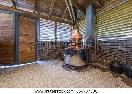 Cauldron for brandy in modern log cabin interior - stock photo