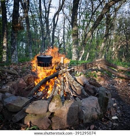 Cauldron hanging over burning campfire - stock photo