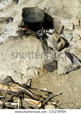 Cauldron outdoors / Cauldron with boiling water over bonfire outdoors with rocky and woody natural background - stock photo