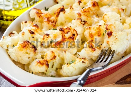 Cauliflower and cheese gratin in the baking dish on wooden table closeup - stock photo