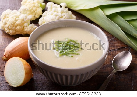 Cauliflower soup with leek on wooden background. Selective focus. Copy space