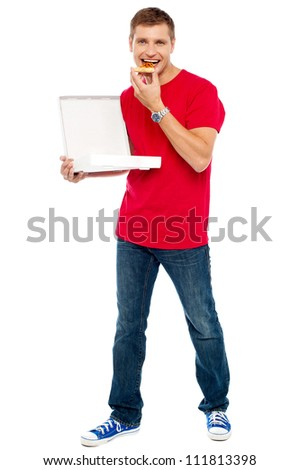 Causal  smart guy holding pizza box and eating a piece. Full length portrait
