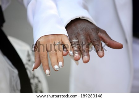 Causian and African-American couple holding hand with ring - stock photo