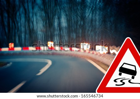 caution - curvy road at night Caution - driving on a curvy country road. - stock photo