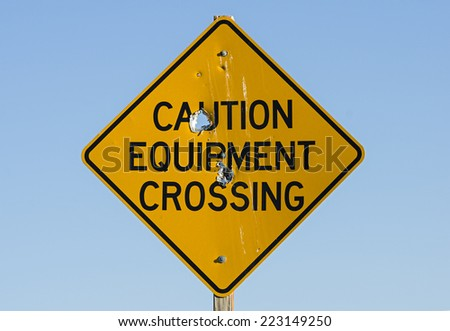 caution equipment crossing road sign with bullet holes