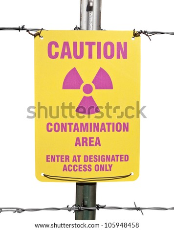 Caution radioactive contamination warning sign with barb wire fence isolated. - stock photo