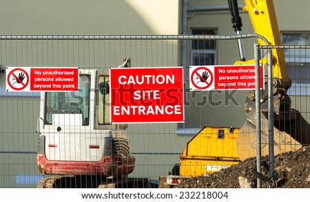 Caution sign at entrance to construction site.Red plaque hanging on the fence in the middle between the two arrays speaking about the ban on entry to the site. - stock photo