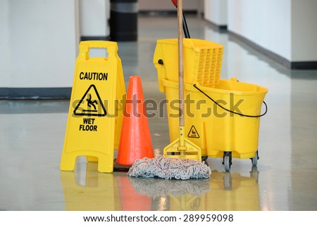 Caution sign with mop and bucket on office floor - stock photo