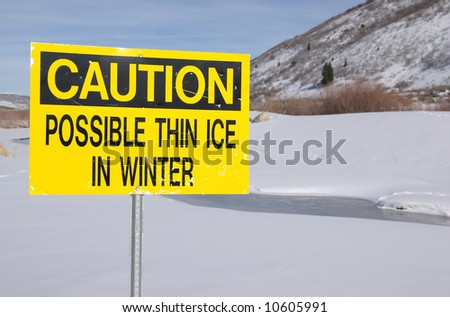 Caution Thin Ice sign next to a frozen pond.