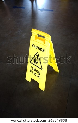 Caution yellow sign for warning, falling in love, on a floor