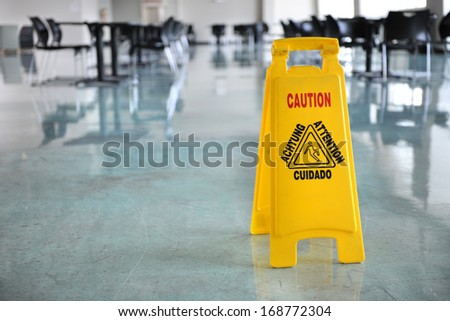 Caution yellow sign inside building hallway - stock photo