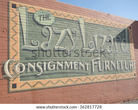 Cave Creek, Arizona, USA - 14.01.2016: Lazy Lizard consignment furniture advertisement on wall of the shop in retro American style town of Cave Creek.