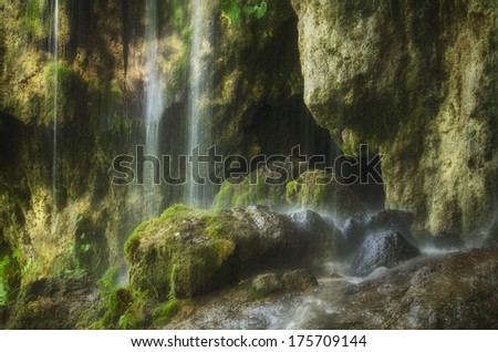 cave entrance with waterfall - stock photo