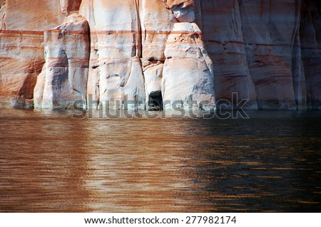 Cave like crevice in the cliff adds interest to a towering wall of sandstone. - stock photo