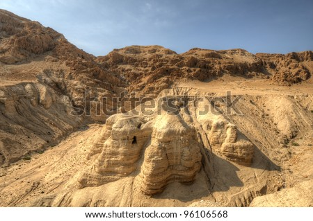 Cave of the Dead Sea Scrolls, known as Qumran cave 4, one of the caves in which the scrolls were found at the ruins of Khirbet Qumran in the desert of Israel. - stock photo