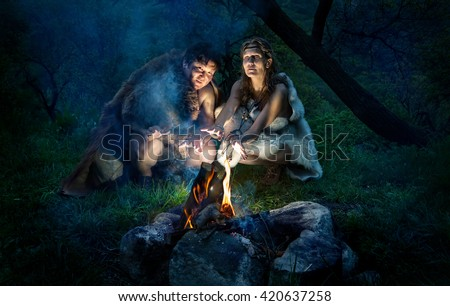 Cave people dressed in animal roast oneself at bonfire in the forest