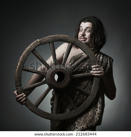 Caveman wearing leopard skin hold old wooden wheel. - stock photo