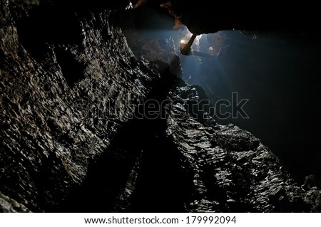 Caver, spelunker abseiling in a deep pothole  - stock photo