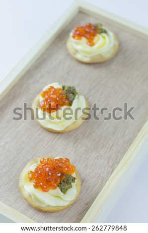 Caviar appetizers with pesto cream cheese and crackers - stock photo