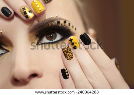 Caviar manicure in yellow and black nail Polish on the girl with false eyelashes and rhinestones of different shapes. - stock photo