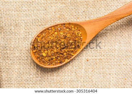 cayenne pepper spice in spoon on a sackcloth - stock photo