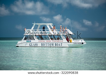 Cayo Coco island, Cuba, Aug 31, 2015, amazing gorgeous stunning view of glass boat with people on board going in tranquil, azure ocean near the beach on sunny day