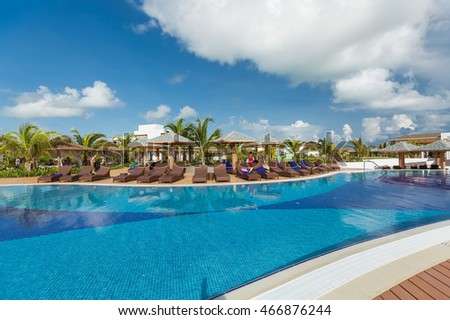 Cayo Guillermo island, Cuba, June 28, 2016, amazing gorgeous view of swimming pool with comfortable stylish sunbeds and people relaxing and enjoying their vacation time on sunny beautiful day