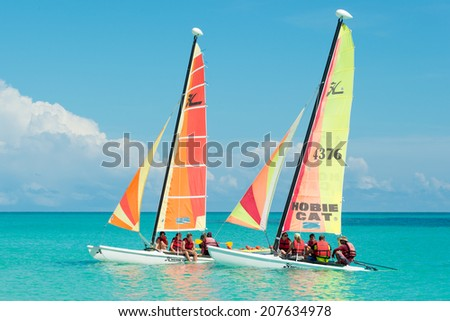 CAYO SANTA MARIA, CUBA - JULY 15, 2014 : Tourists sailing in colorful catamarans on a beautiful sunny day at the key - stock photo
