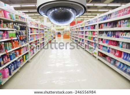 CCTV and blurred supermarket ,The CCTV Security Camera operating in counter service cashier at supermarket store blur background. Business protection. - stock photo